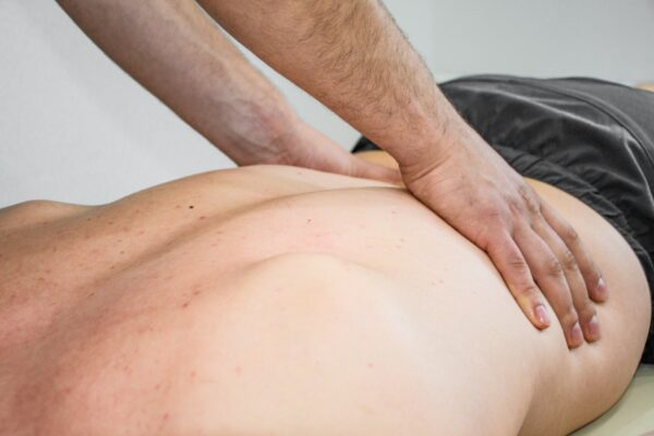 Personal trainer massaging a man's back as part of a rehabilitation therapy. Back pain, massage.